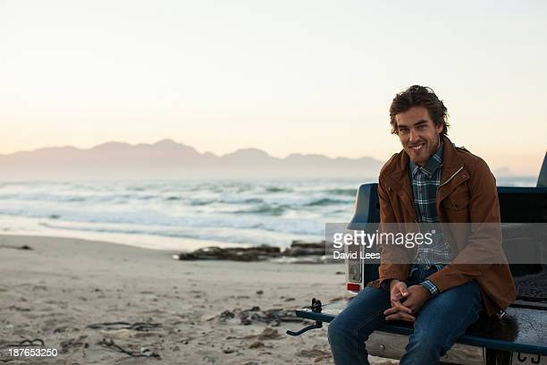 Man at beach sitting in back of truck