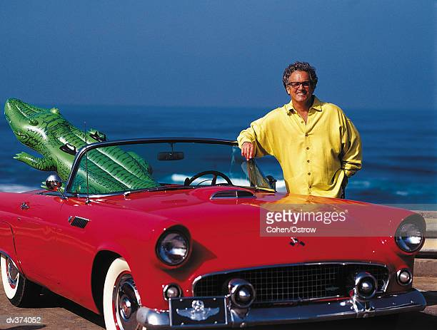 man at beach with inflatable alligator in his red convertable car - novelty item stock pictures, royalty-free photos & images