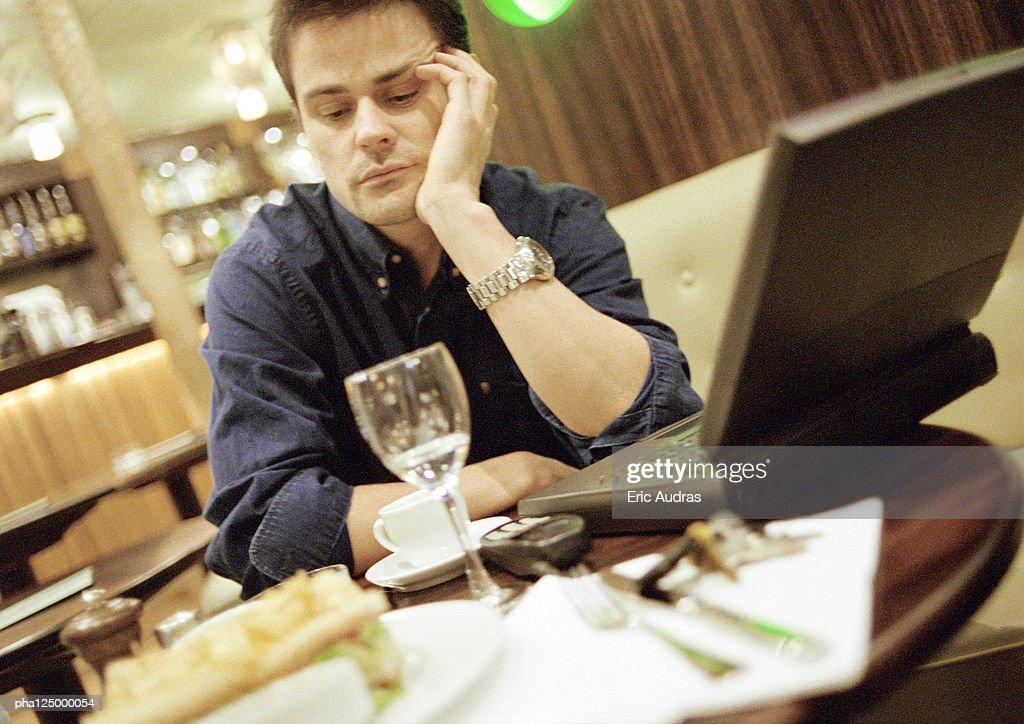 Man at cafe table, using laptop computer : Stockfoto