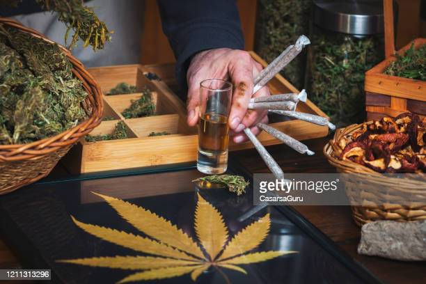 man at cannabis store holding and offering cannabis liquor and marijuana joints in hand - cannabis store stock pictures, royalty-free photos & images