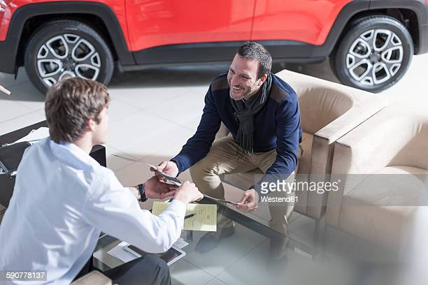 Man at car dealership looking at brochure