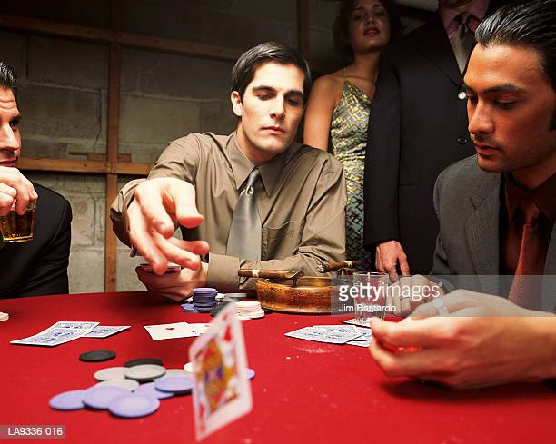 Man at card game throwing playing card across table
