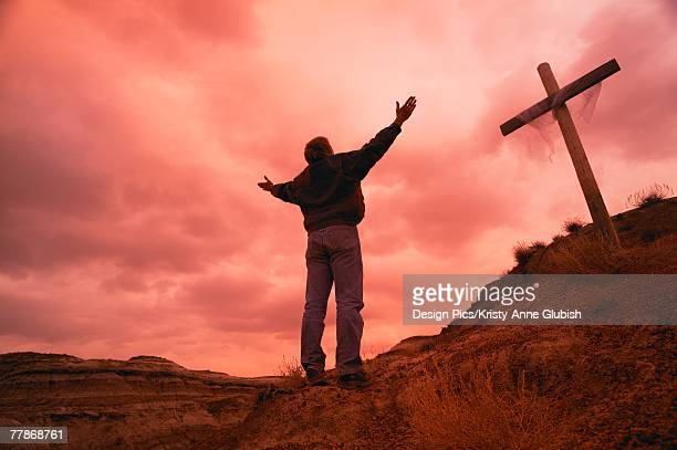 Man at cross with raised arms