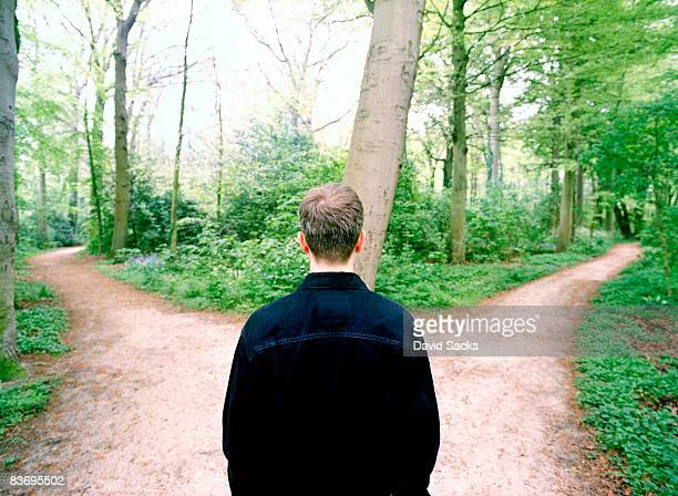 man at crossroads - forked road stock pictures, royalty-free photos & images