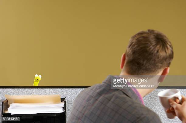 man at cubicle desk looking at puppet - novelty item stock pictures, royalty-free photos & images