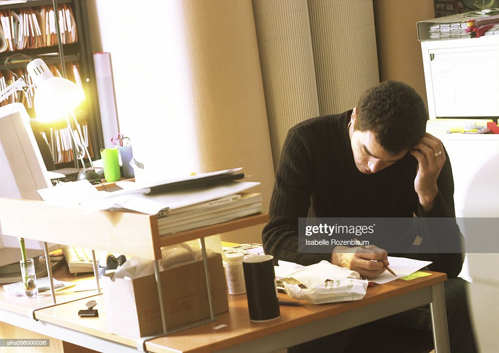 Man at desk examining a paper : Stockfoto