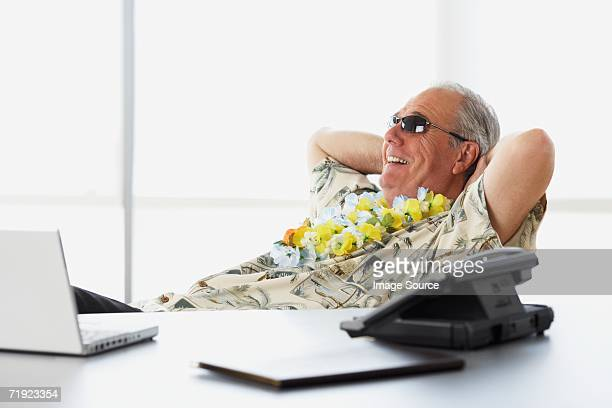 Man at desk in hawaiian outfit
