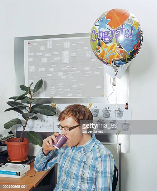 Man at desk in office drinking coffee by 'congrats' helium balloon