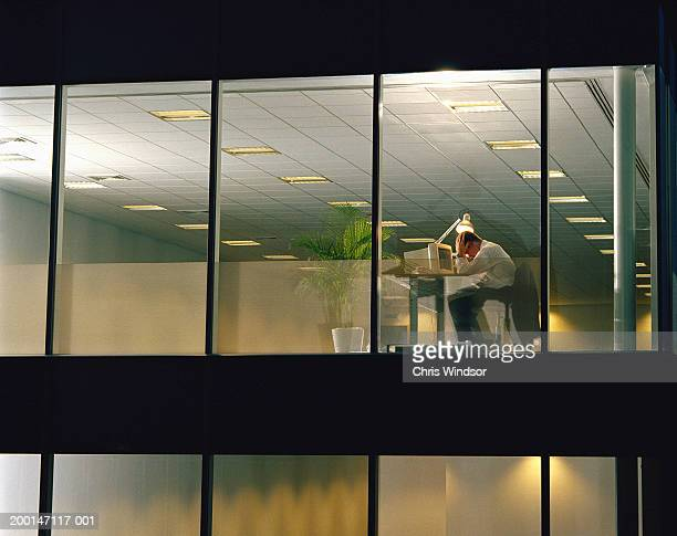 Man at desk in office, head in hands, view through window, night