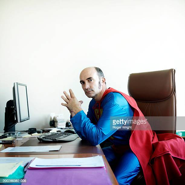 man at desk in superhero costume, portrait - cape stock pictures, royalty-free photos & images