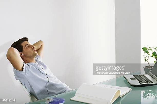 Man at desk leaning back with hands behind head, listening to earphones and whistling