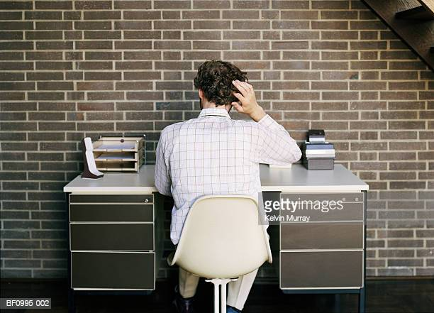 Man at desk scratching head, rear view
