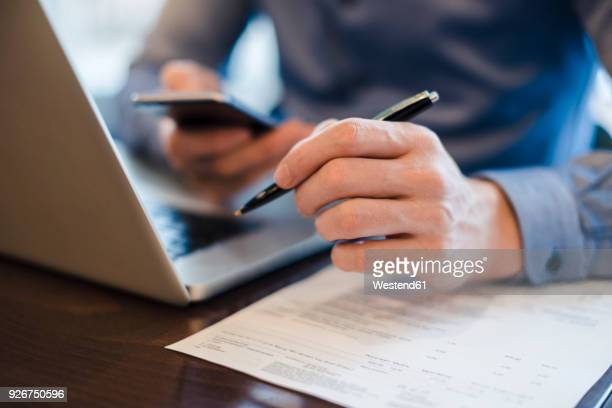 man at desk using cell phone and holding ball pen in his hand, close-up - linkshandig stockfoto's en -beelden