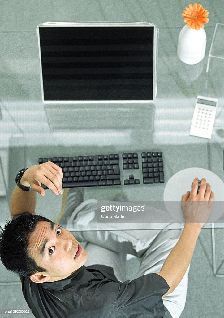Man at desk with futuristic devices, high angle view, portrait : Stockfoto