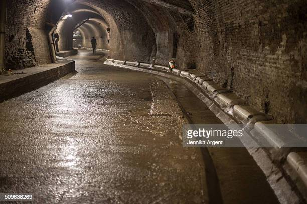man at end of winding underground tunnel