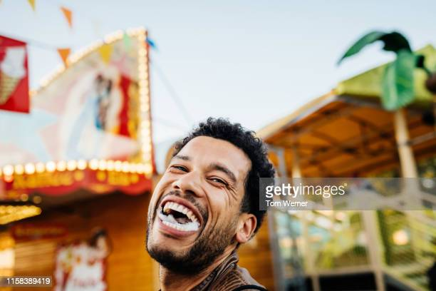 man at fun fair laughing with mouthful of candy floss - 遊園地 ストックフォトと画像