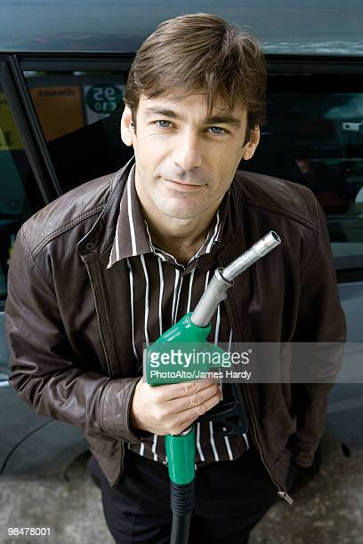 Man at gas station holding gas nozzle