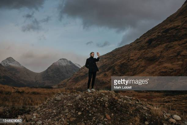man at glen etive in the highlands of scotland taking a picture - strathclyde stock pictures, royalty-free photos & images