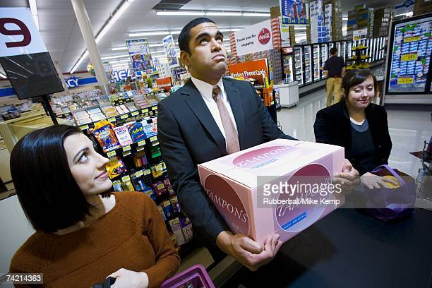 Man at grocery checkout with box of tampons and two women