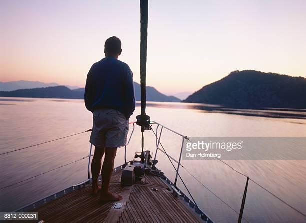 Man at Helm of Boat at Sunset