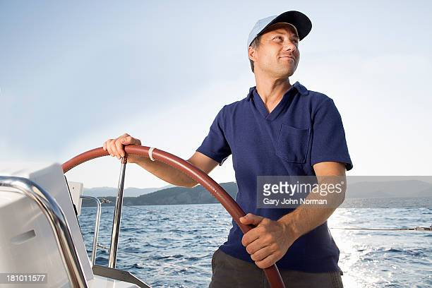 man at hem of sailing yacht