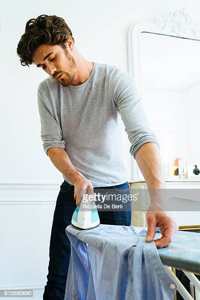 Man At Home Ironing His Shirt