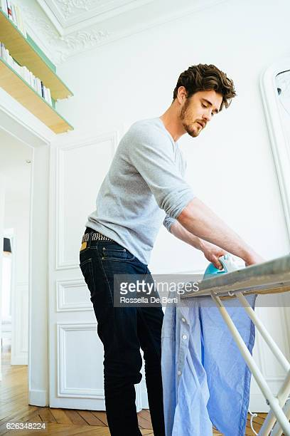 Man At Home Ironing His Shirt