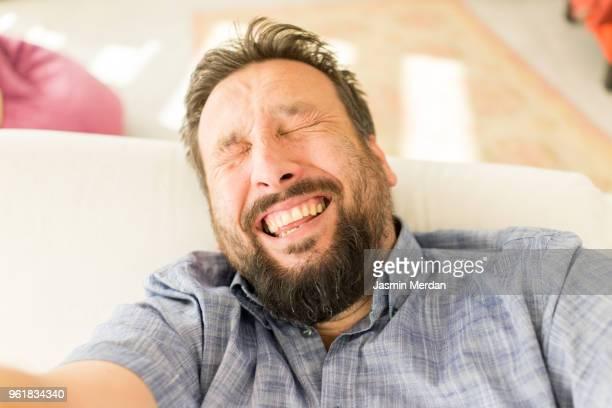 Man at home laughing