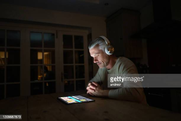 man at home listening to music on a tablet computer with headphones at nighttime - stream stock pictures, royalty-free photos & images
