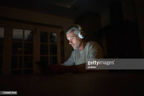 man at home listening to music with headphones at night - producer stock pictures, royalty-free photos & images