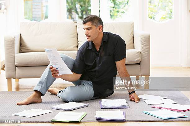 Man at home looking at financial papers