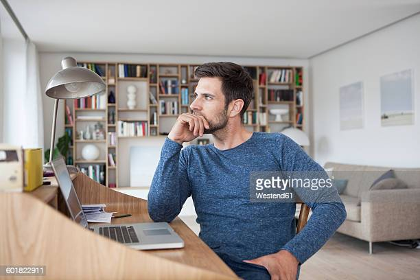 man at home looking away from laptop - hommes d'âge moyen photos et images de collection