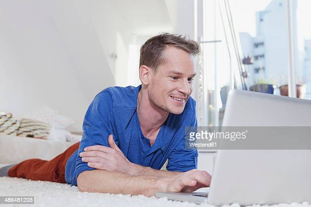 Man at home lying on carpet and using laptop
