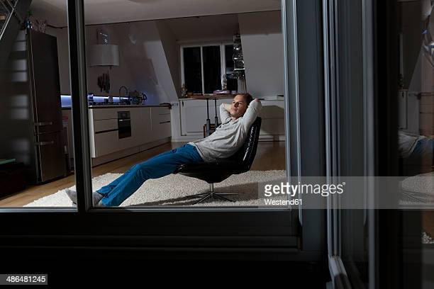 Man at home relaxing in armchair at night