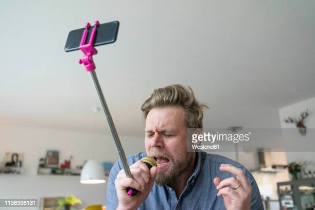 man at home singing into microphone attached to a selfie stick - man made stock pictures, royalty-free photos & images