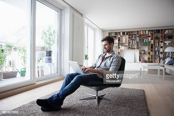Man at home sitting in armchair using laptop