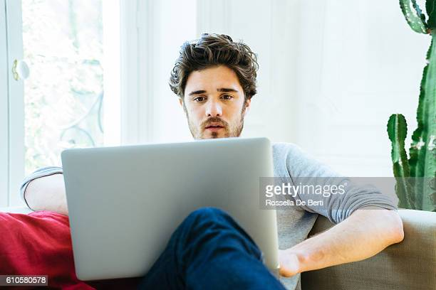Man at home sitting on couch using laptop