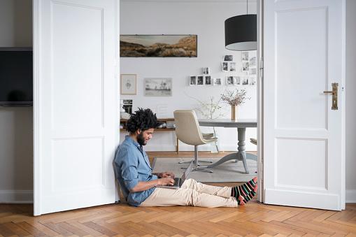 Man at home sitting on floor working with laptop in door frame - gettyimageskorea