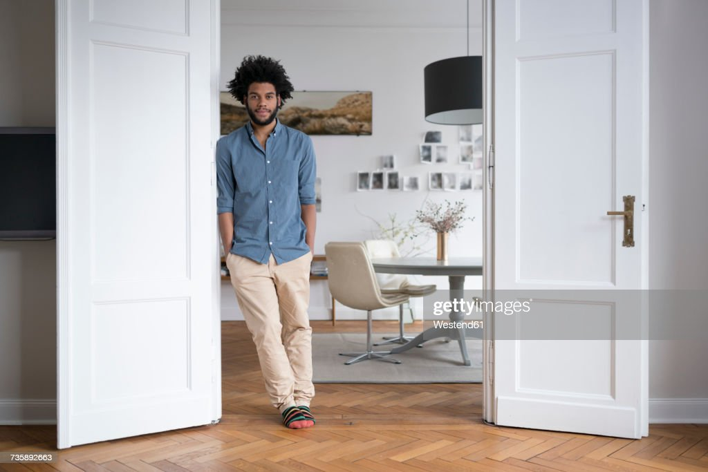 Man at home standing in door frame in living room : Stock Photo