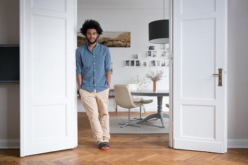 Man at home standing in door frame in living room - gettyimageskorea
