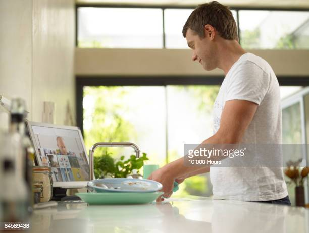 Man at home video conferencing whilst washing up