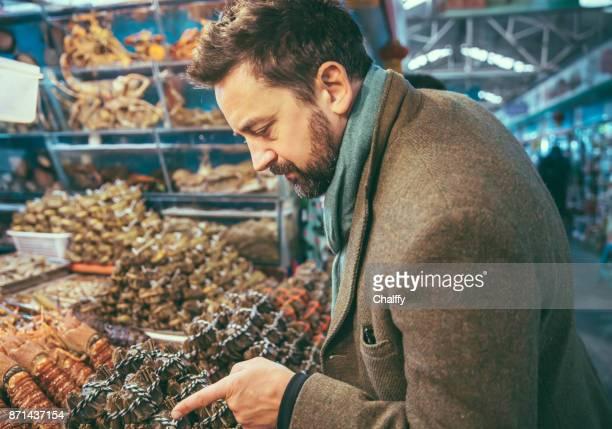 Man at Market Buying Fishes