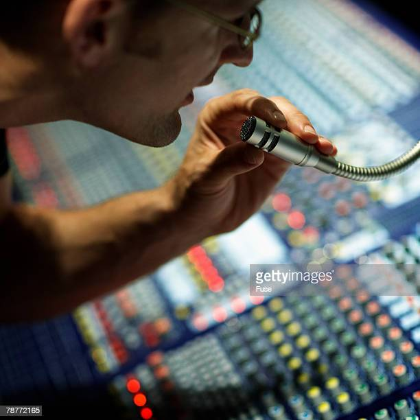 Man at Mixing Console Talking into Microphone
