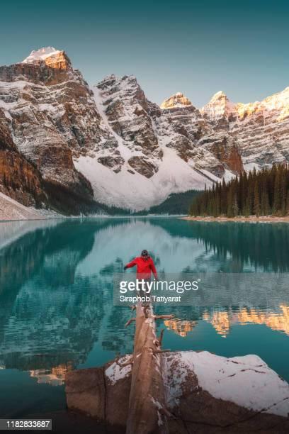 man at moraine lake at sunrise, banff, canada - montañas rocosas canadienses fotografías e imágenes de stock
