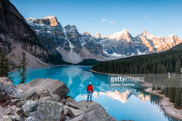man at moraine lake at sunrise, banff, canada - canadian rockies stockfoto's en -beelden