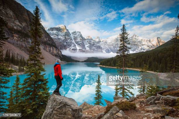 man at moraine lake in autumn, banff, canada - travel stock pictures, royalty-free photos & images