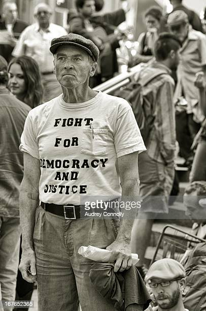 "Man at Occupy Wall Street demonstrations in Zoccati Park, Manhattan with ""fight for democracy and justice"" t-shirt on."