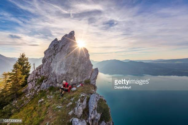 man at outdoor cooking  with view to lake attersee from schober- sunset at mount schoberstein, alps - upper austria stock pictures, royalty-free photos & images