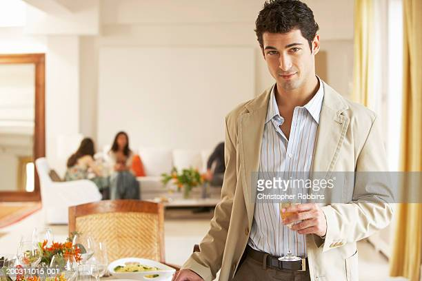 man at party holding drink, portrait, friends in background - beige suit stock pictures, royalty-free photos & images