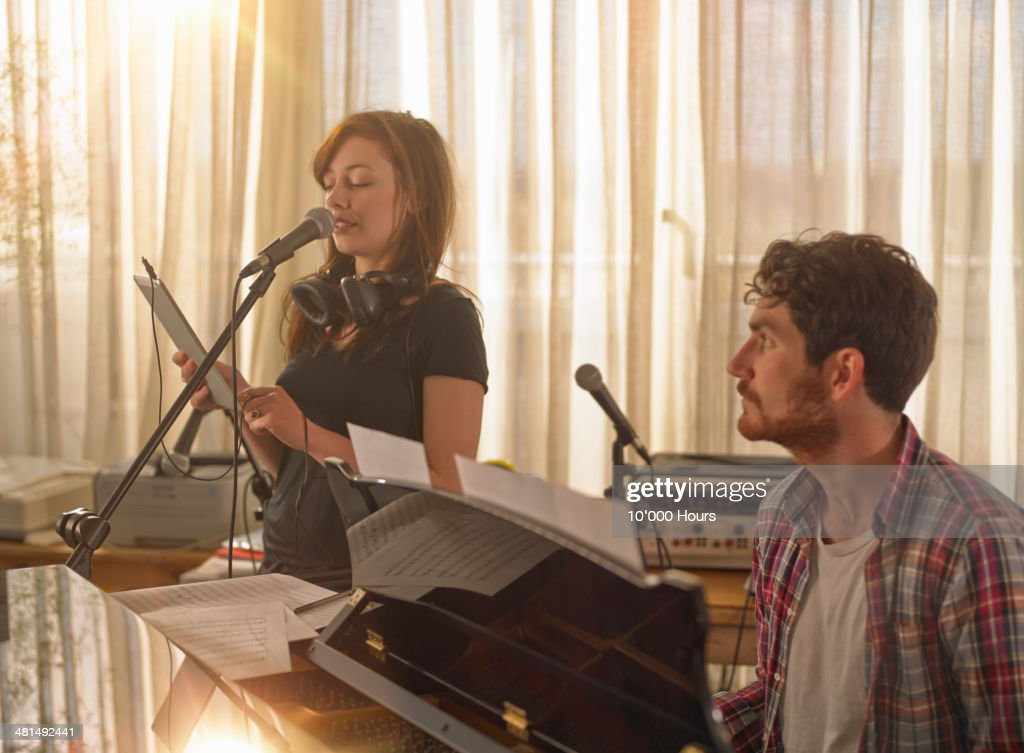 Man at piano, woman singing holding tablet compute : Stock Photo